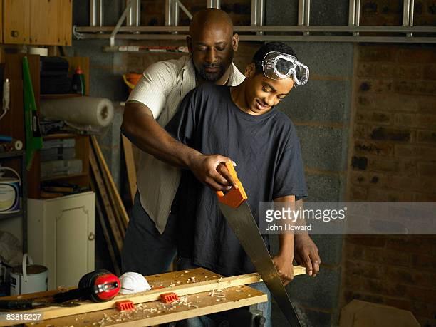Vater und Sohn mit Holzarbeiten dass Teenager