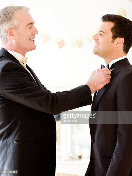 Father helping the groom straighten his bow tie