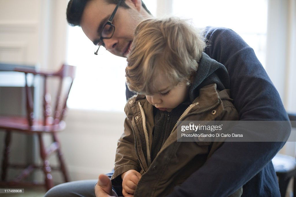 Father helping toddler son zip jacket