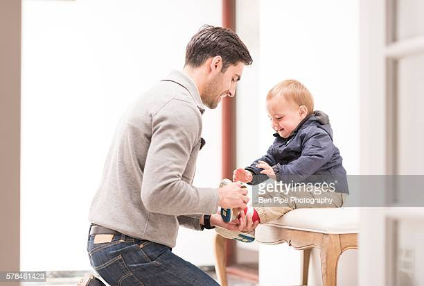 Father helping young son put shoes on