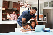 Father Helps Children With Homework Whilst Mother With Baby Uses Laptop In Kitchen