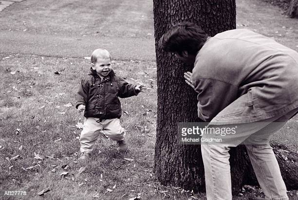 Father hiding from toddler (2-3) behind tree (B&W)
