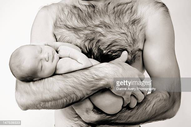 Father hold naked sleeping newborn baby