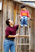 Father holding a ladder with son sitting on top