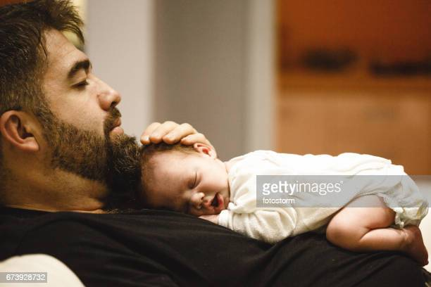 Father holding a sleeping newborn baby