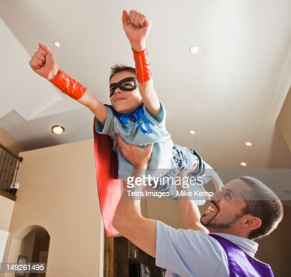 Father holding aloft his son (8-9) dressed up in fancy dress costume : Stock Photo