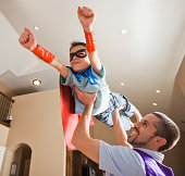 Father holding aloft his son (8-9) dressed up in fancy dress costume