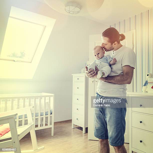 Father holding and hugging little baby boy tenderly, baby's room