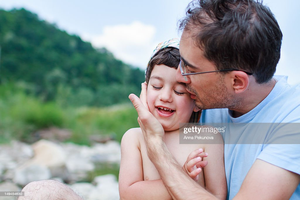Father holding and kissing his son : Stock Photo