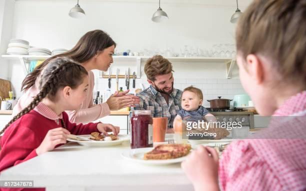 Vater holding Babyjungen am Frühstückstisch, Mutter klatschte und ihm unterhaltsam