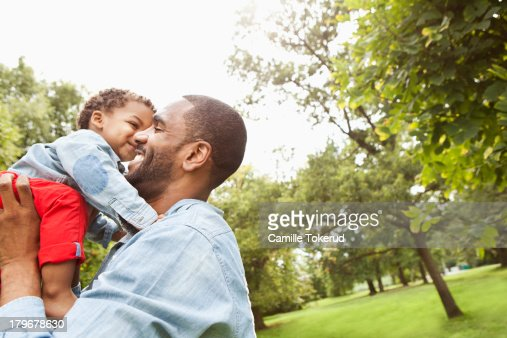 Father holding baby boy in park : Stock Photo