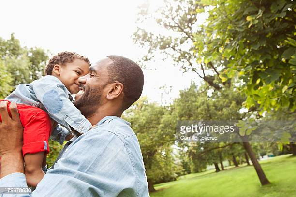 Father holding baby boy in park