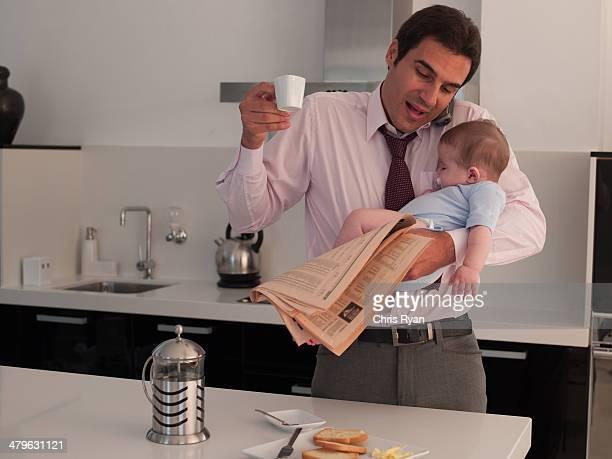 Padre sostiene hija bebé mientras hablando por teléfono en la cocina