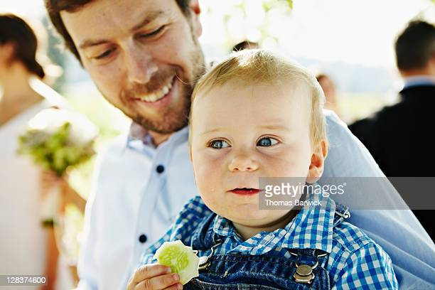 Father holding baby eating cucumber at wedding
