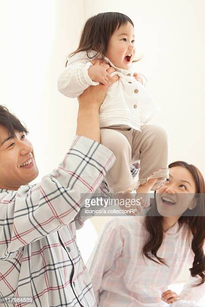 Father Holding Baby Girl Aloft, Mother Watching