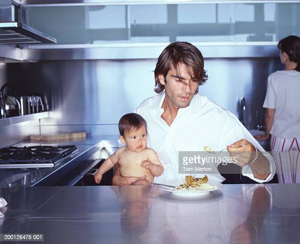 Father holding baby girl (6-9 months) and fork of food