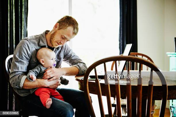 Father holding baby girl on lap at dining table