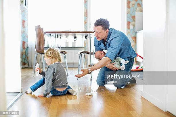 Father holding baby girl while cleaning floor with daughter at home