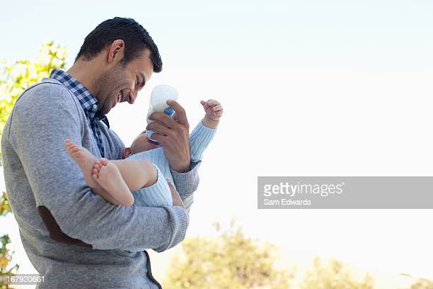 Father holding baby outdoors