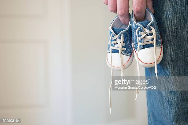Father holding baby sneakers