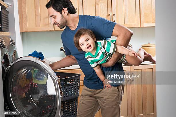 Father holding baby son and doing laundry