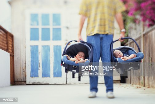 Father holding baby twins (10-12 months) in car seats, low section