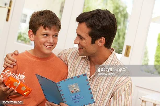 Father holding card by son  (10-12) holding present, smiling