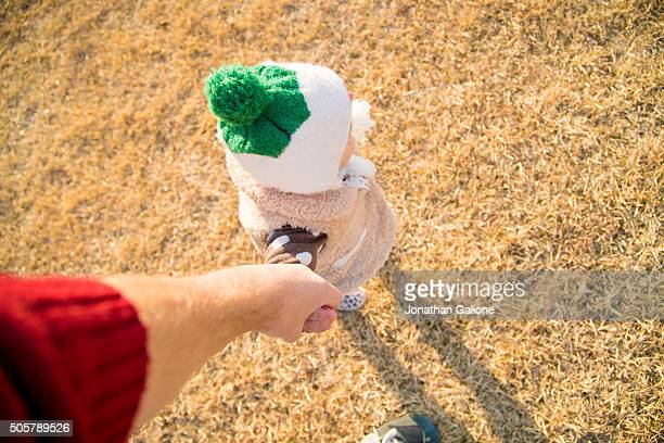 POV of father holding child's hand and walking together