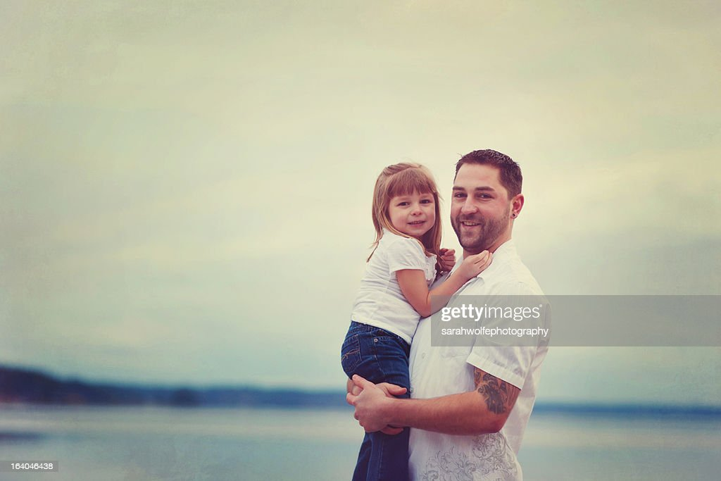 father holding daughter on beach : Stock Photo