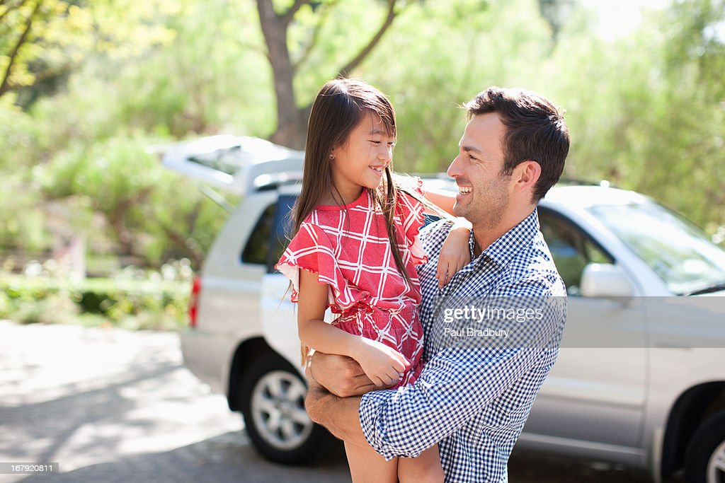 Father holding daughter outdoors : Stock Photo