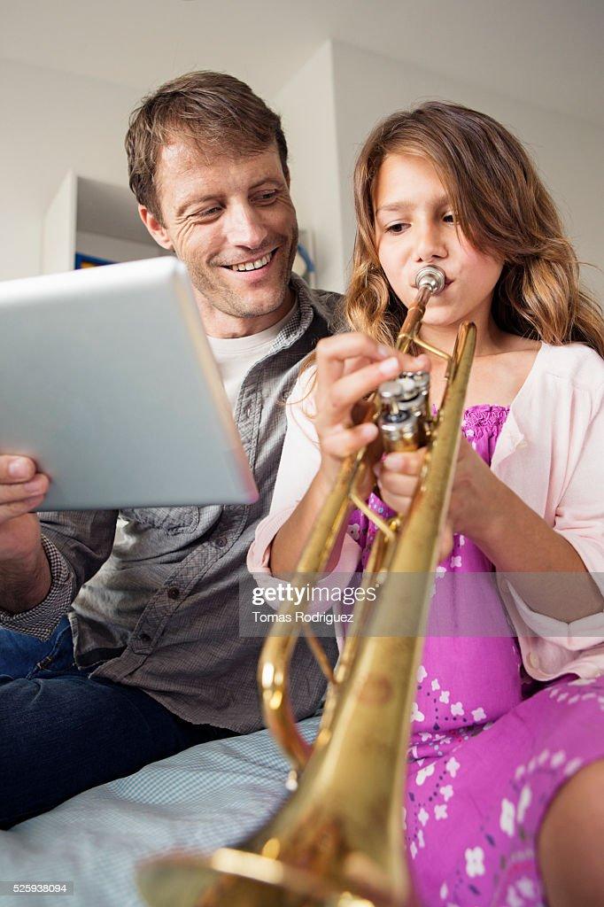 Father holding digital tablet for daughter (8-9) playing trumpet : Bildbanksbilder