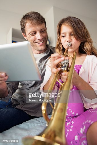 Father holding digital tablet for daughter (8-9) playing trumpet : Bildbanksbilder