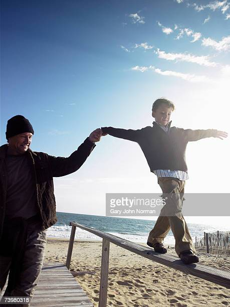 Father holding hand of son (6-8) balancing on railing