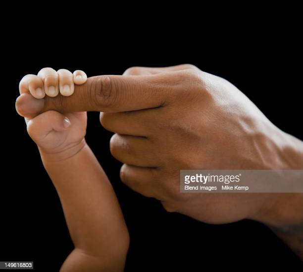 Father holding hands with newborn baby