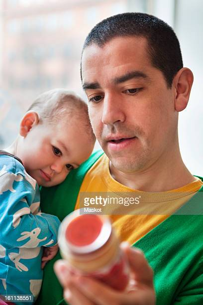 Father holding his daughter (0-11 months) and a jar of baby food