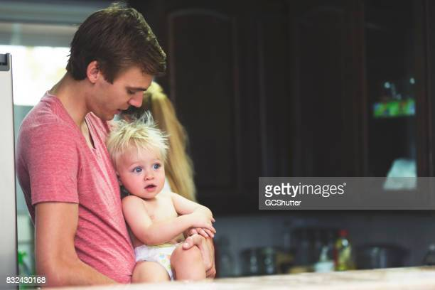 Father holding his son close in the kitchen