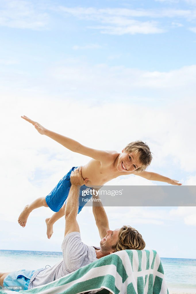 Father holding his son (10-12) mid-air while relaxing on deckchair on beach : Stockfoto