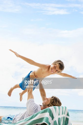 Father holding his son (10-12) mid-air while relaxing on deckchair on beach : Stock-Foto