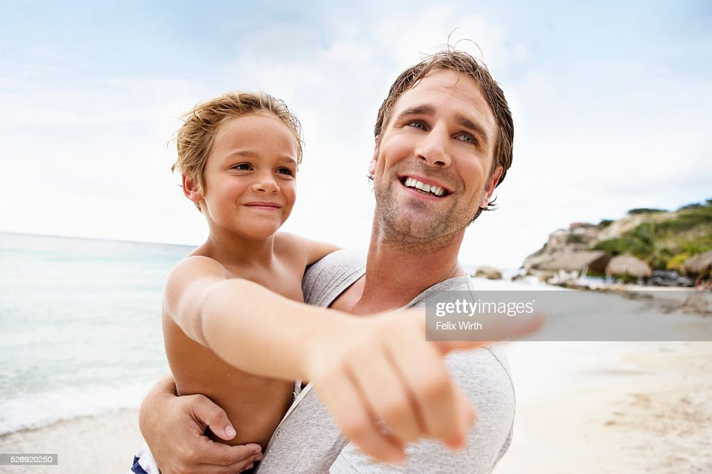 Father holding his son (4-5) on beach : Stockfoto