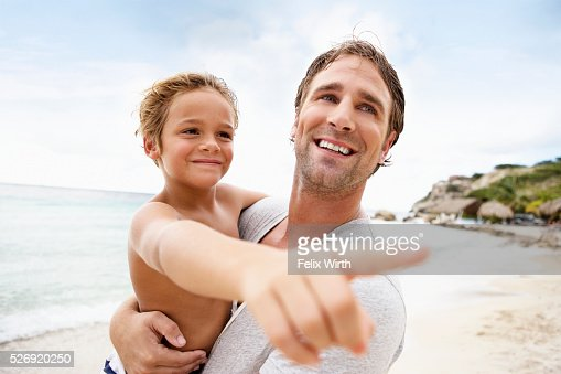 Father holding his son (4-5) on beach : Foto de stock