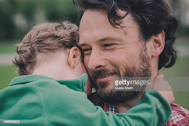 Father holding his young boy closely.