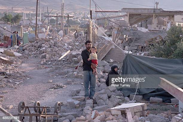 A father holding his young son stands among rubble Their town was laid waste after being struck by a severe earthquake Casualty estimates have...