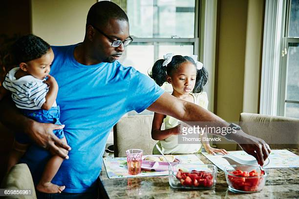 Father holding infant son while serving breakfast