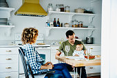 Father holding infant while dining with wife