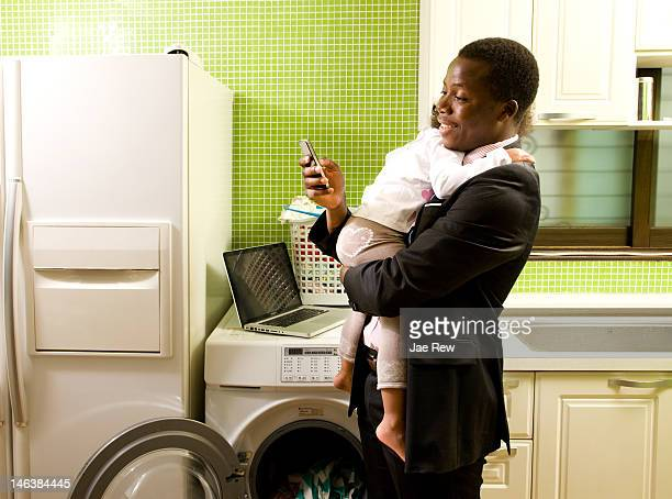 Father holding kid and using smart phone in  kitch