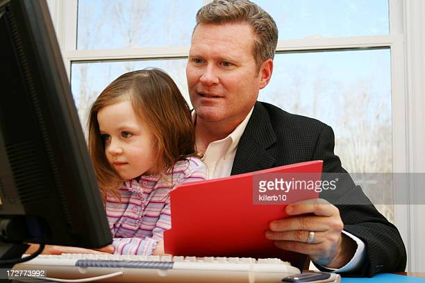 Father holding red envelope with daughter on lap at computer