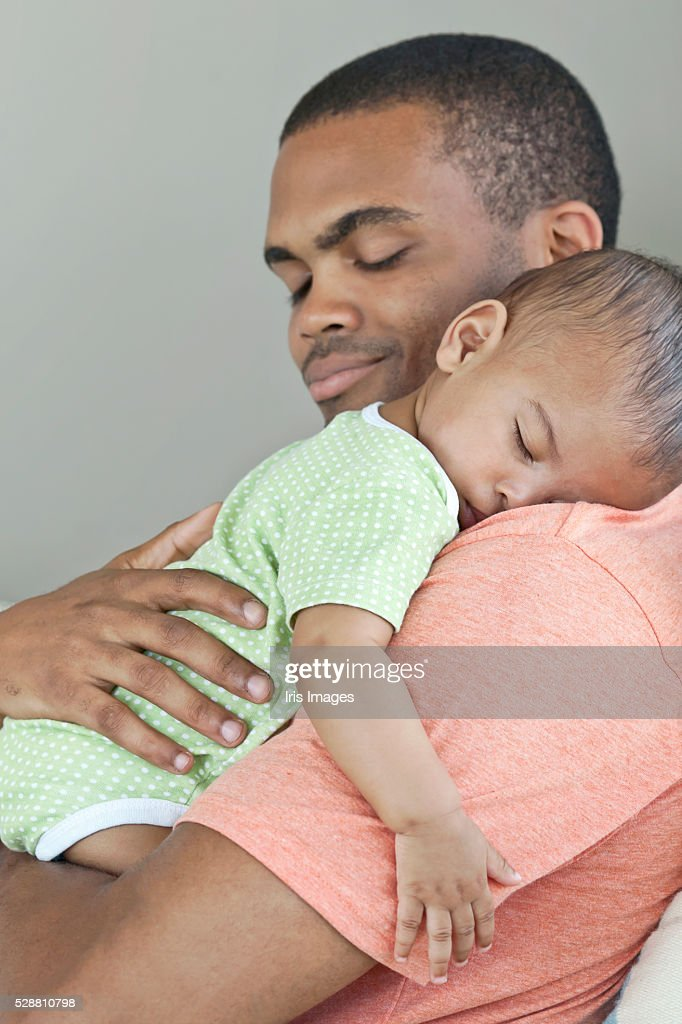 Father holding sleeping son (6-12 months)