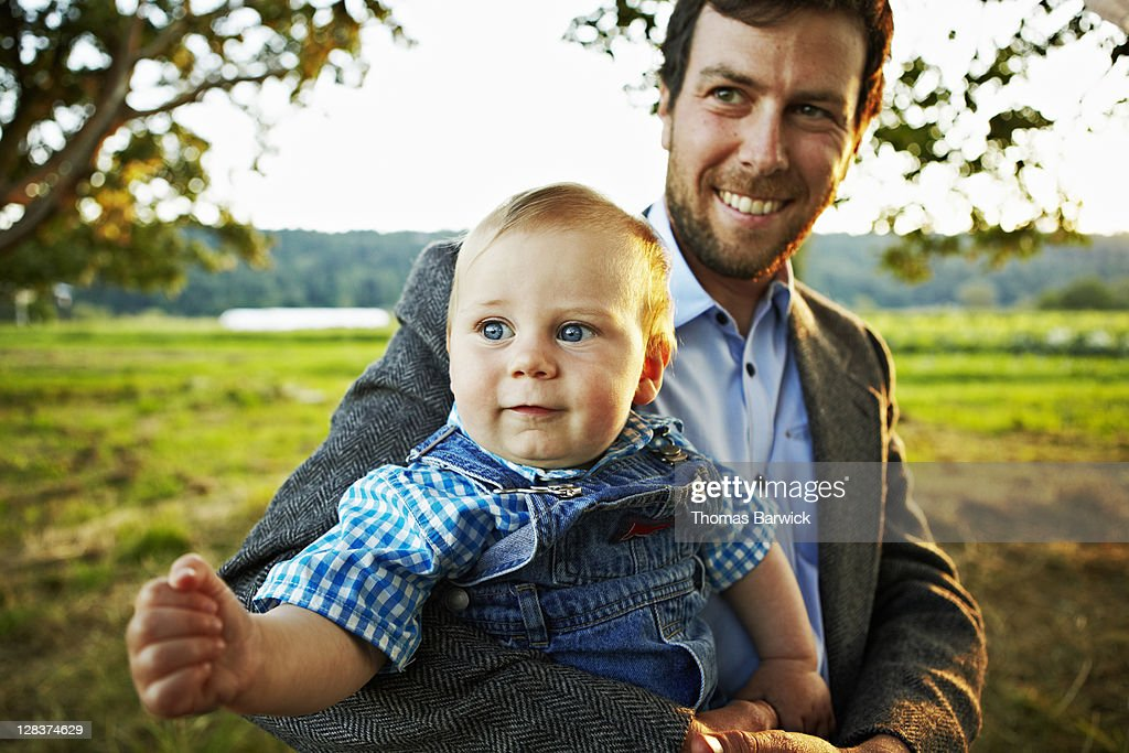 Father holding smiling baby boy at sunset : Stock Photo