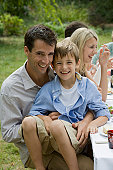 Father Holding Son at Family Picnic