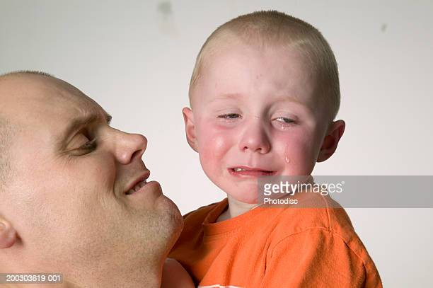 Father holding son (6-7), crying, posing in studio, close-up, portrait